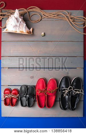 Family Boat Shoes On Wooden Background. Four Pair Of Red And Black    Grey Desk With Rope  Shell. To