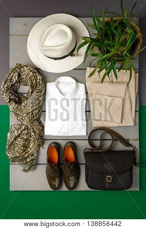 Women's Outfit On Wooden Background. Fashion Clothes. Beige Straw Hat,  Pant, White Shirt, Green Sca
