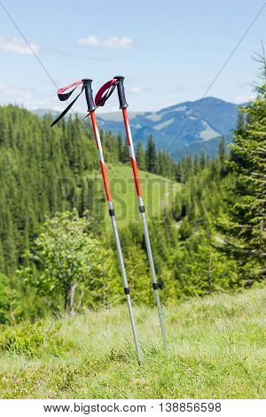 Pair of trekking poles made from three aluminum sections on a background of forested mountains
