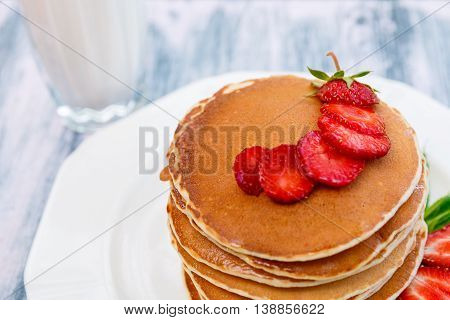 Closeup of pancakes with fresh strawberry and mint near glass with milk on white plate on pink wooden background. Stack of pancakes on the table.