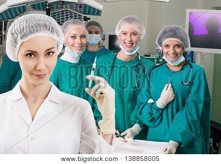 Young female anesthetist with syringe on the surgery team background