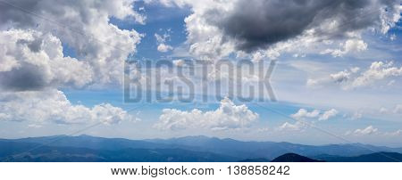 Panorama of a sky with cumulus and storm clouds over the mountain ranges