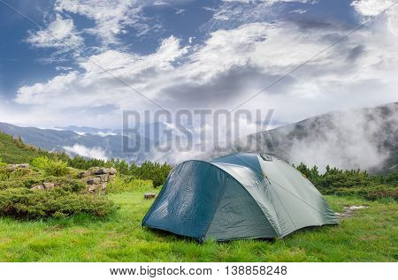 Green tunnel hiking tent after the storm on the background of a mountains and sky with swirling clouds