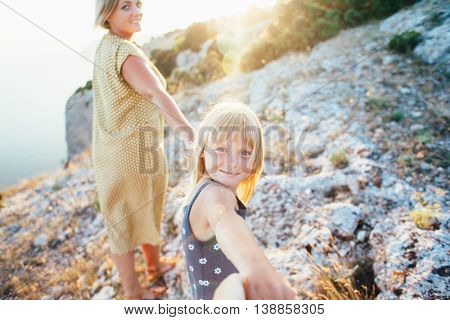 Mom walking with her child on top of the mountain in sunlight