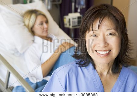 Doctor Standing In Patients Room,Smiling