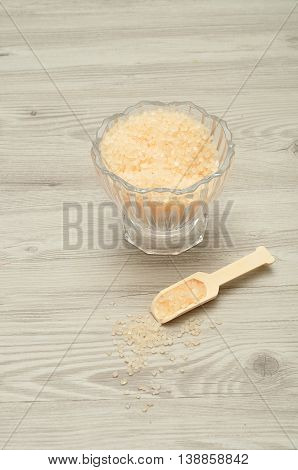 A bowl of bath salt displayed with a wooden spoon