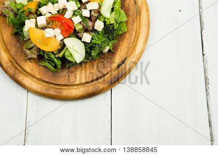 Fresh Vegetable Salad With Greenery, Cheese, Tomatoes, Cucumber On A White Wooden Table