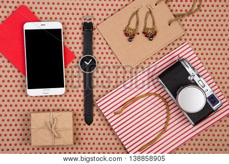 Shopping Bag, Gift Box, Smart Phone, Camera, Watch, Notepad And Women's Jewelry On Craft Paper Backg