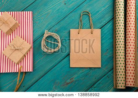 Celebratory concept - set with handmade striped shopping bag gift bags packing paper with polka dots on blue wooden background