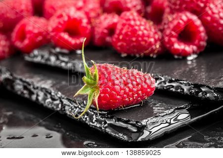 Fresh red raspberry on a wet slate backround