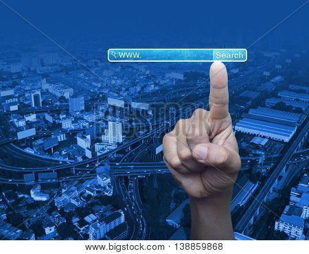 Hand pressing search www button over city tower background Searching system and internet concept