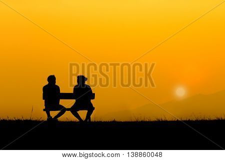 A silhouette of sweetheart on the bench in sunset