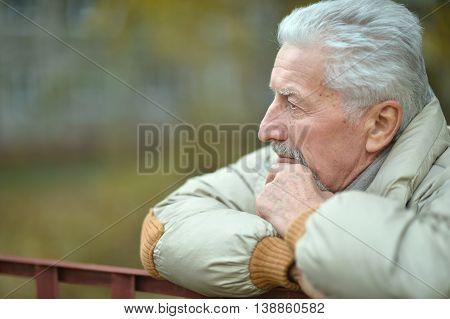 portrait of sad senior man  in  park