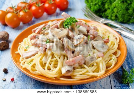 Spaghetti with Bechamel sauce mushrooms and bacon on a wooden table