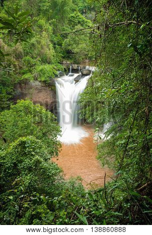Focusing on big waterfall with mud water through green tree in tropical forest