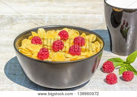 Breakfast in the garden on a sunny summer day. Bowl with corn flakes and raspberries mug with milk on a background grey wooden table close-up