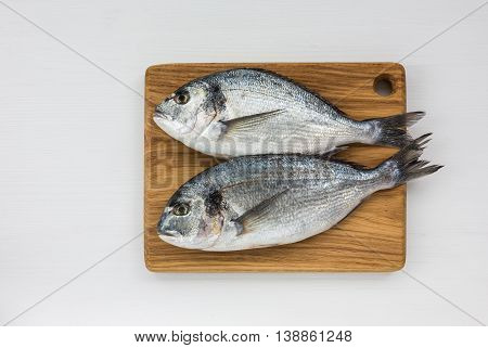Fresh Dorado Fish On Wooden Cutting Board On White Table. Top View, Copy Space.