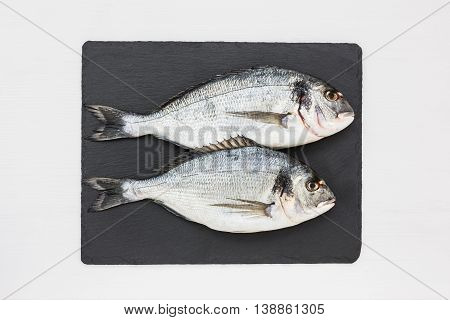 Fresh Dorado Fish On Slate Cutting Board On White Table. Top View, Copy Space