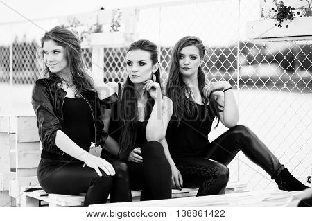 Portrait Of Three Fashion Girls Sitting On Bench At Pier