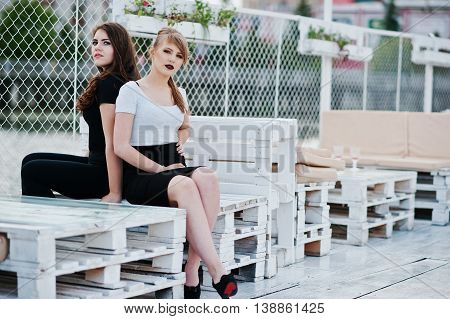 Portrait of two girls sitting on bench at pier