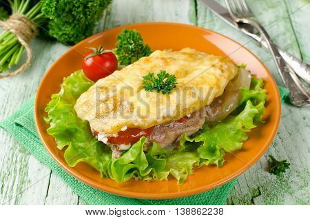 Pork chop with tomatoes potatoes and cheese on a wooden table