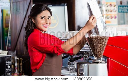 Barista in Indian cafe filling coffee grinder with coffee beans