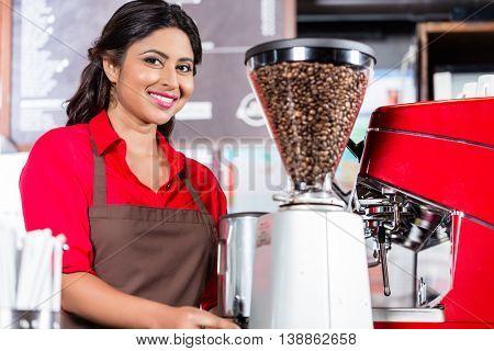 Female barista preparing coffee in Indian Cafe