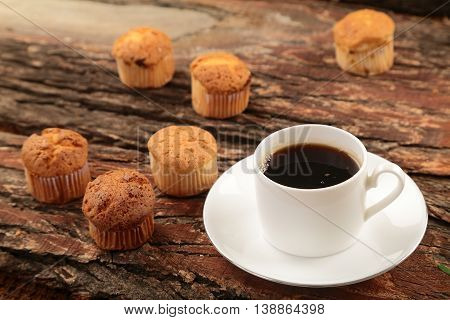 Cup  of coffee and cup cakes on wooden background.