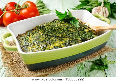 Omelet with nettles and green onions in a ceramic form. Tasty and healthy lunch