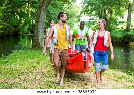 Friends carrying kayak or canoe to forest river
