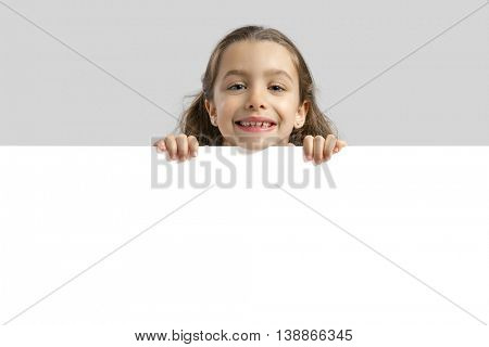 Cute little girl holding a blankboard, with copy space