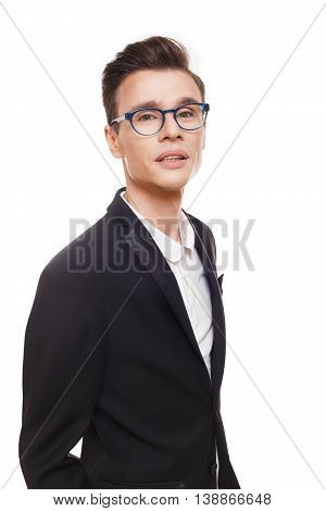 Young stylish man isolated at white. Portrait of confident guy looking at camera. Boy style, trendy male person in eyeglasses and black suit. Modern businessman.