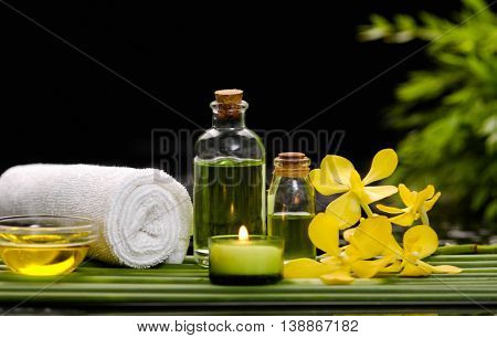 Still life with yellow orchid and candle,oil,towel with row of plant stem