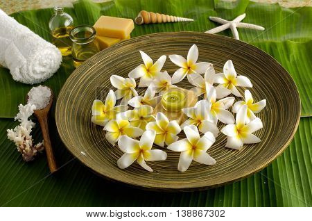 Spa set on banana leaf with frangipani in bowl