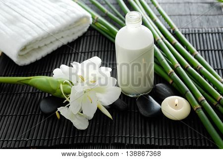 bamboo grove, flower, stones, towel ,oil, candle on mat