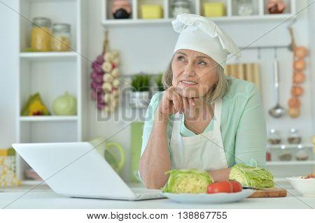 Senior woman portrait at kitchen  with laptop