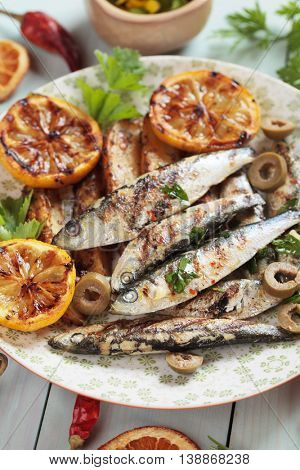 Grilled sardine fish with lemon and green olives