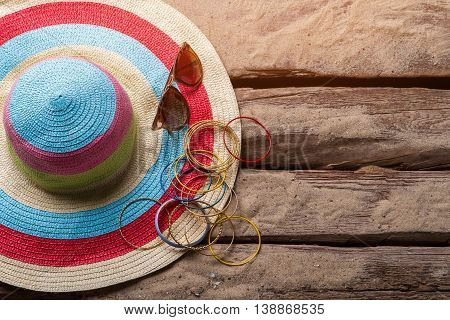 Beach hat and bracelets. Hat with bracelets and sunglasses. Girl's beach accessories. Floor of beach house.