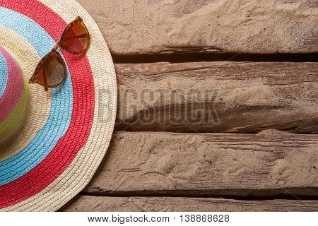 Striped hat and sunglasses. Sunglasses with beach hat. Wooden floor of beach house. Enjoy your vacation.