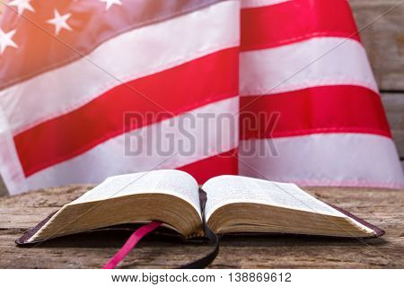 Opened book and USA flag. US flag behind a book. Education is power. You should know your rights.
