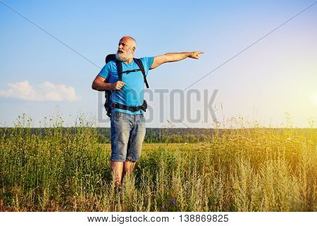 Active aged man with white beard is standing in the field with rucksack and pointing at something in the distance