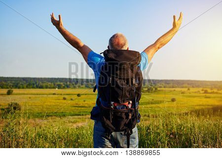 Back view of aged man in casual clothes with rucksack who is standing in the field with his hands lifted enjoying the beauty of meadow landscape