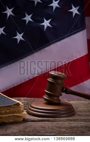 Gavel on American flag background. Old book near gavel. Strong legal system. Find and punish those responsible.