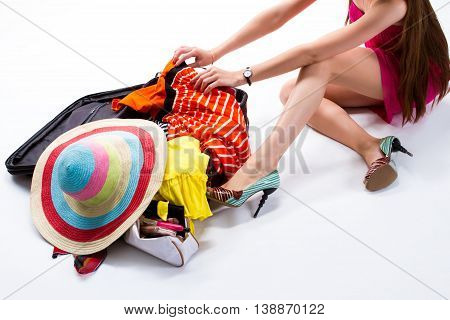 Woman sitting near filled suitcase. Hands touch clothes on suitcase. I can't find summer dress. Lady packing things for trip.