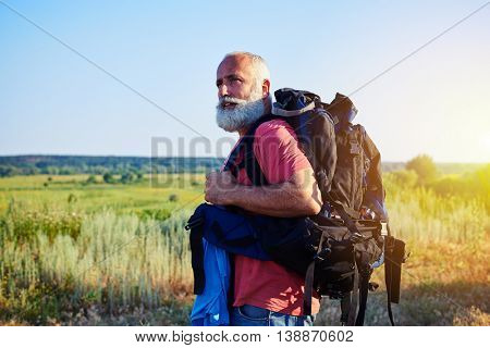 Fit handsome aged man with white beard in casual clothes is standing in front of sunlit field carrying a rucksack