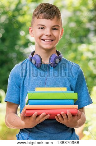 Outdoor portrait of happy teen boy 12-14 year old headphones and books. Back to school concept.
