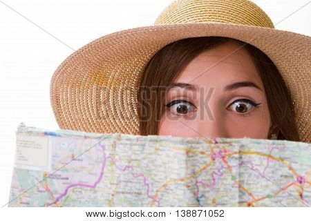 Girl's face behind a map. Scared lady looks at map. Young tourist is lost. This journey scares me.