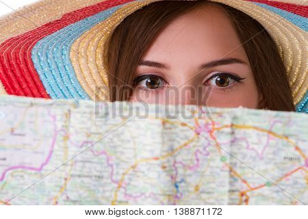 Face of girl behind map. Woman in striped beach hat. Don't get lost during journey. Scared and puzzled.