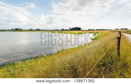 Fence and road on a Dutch dike along a flooded polder area. It is at the end of the afternoon on a sunny day in the summer season.