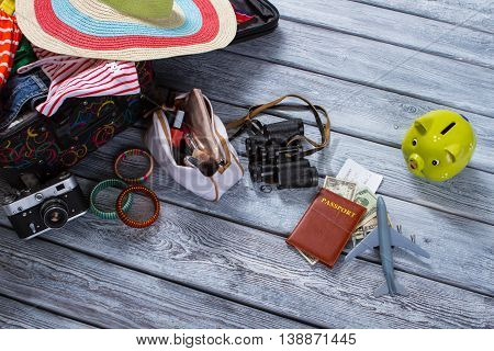 Binoculars and suitcase with clothes. Piggy bank and toy plane. Luggage and document for journey. Things on gray wooden floor.